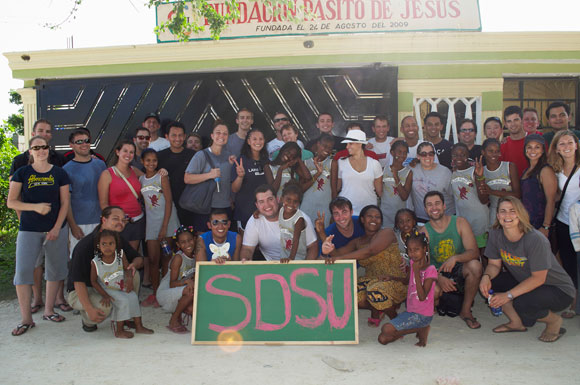 Students and girls living at Fundacion Pasito de Jesus with sign that reads SDSU