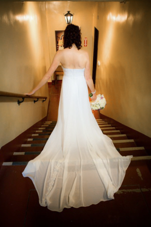 Bride walking down a stairway while holding a bouquet