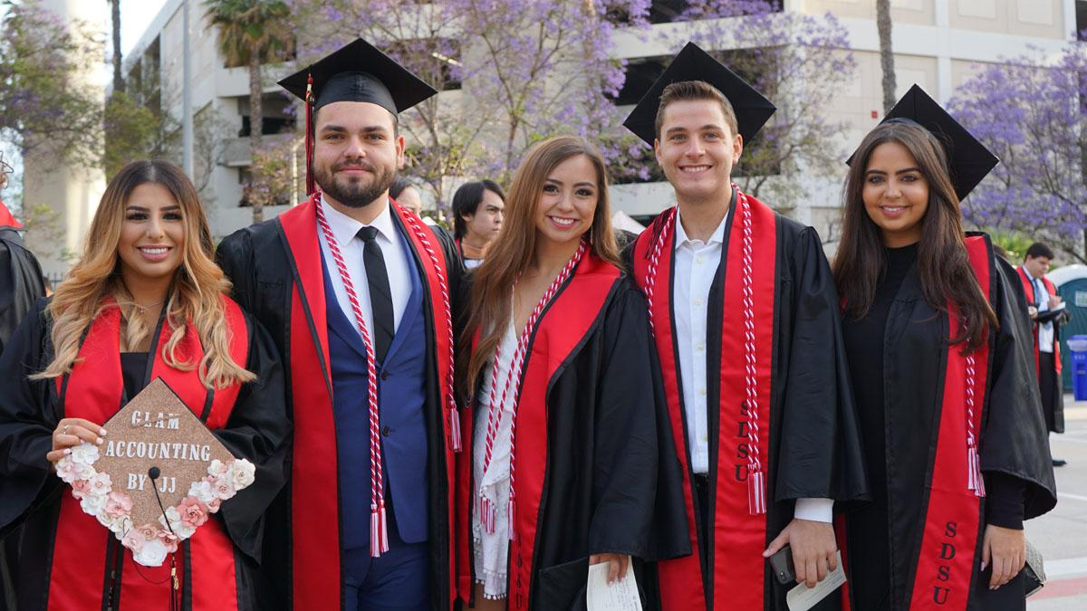 Five students wearing graduation gowns posing for photo