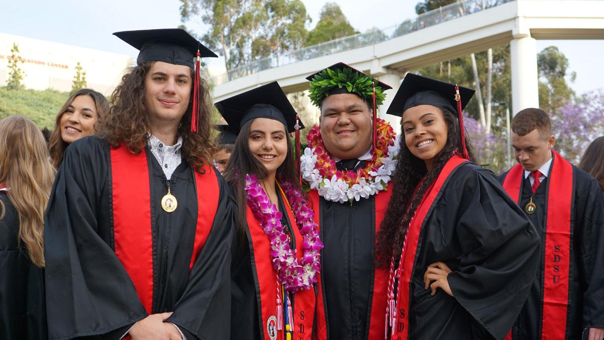 Four students wearing graduation gowns and leis