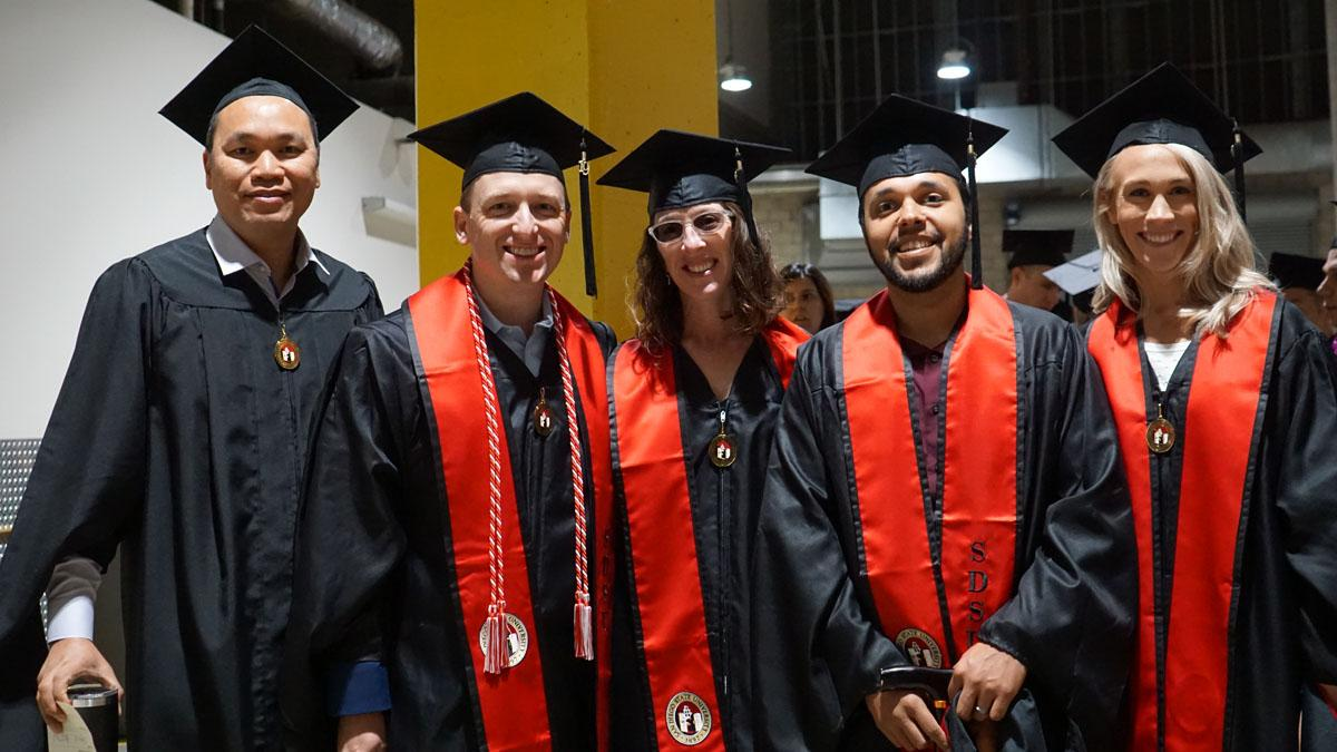 Five students wearing graduation gowns and caps
