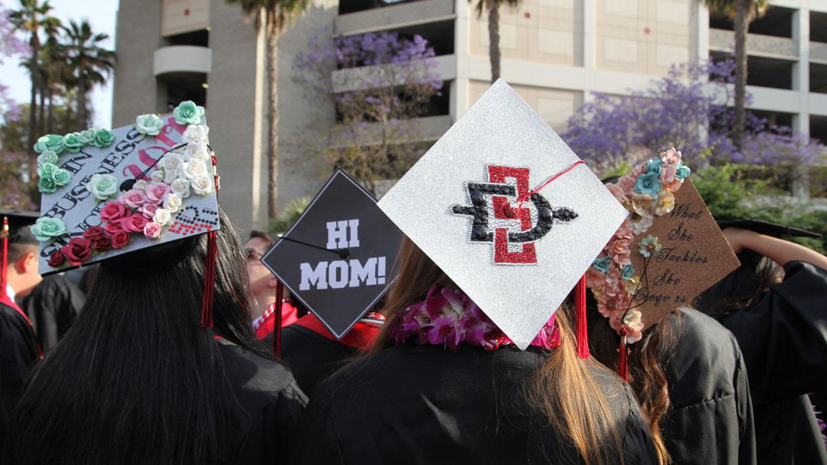 Graduation caps that say 'In Business since 2019' 'Hi Mom' and 'What she tackles she conquers'