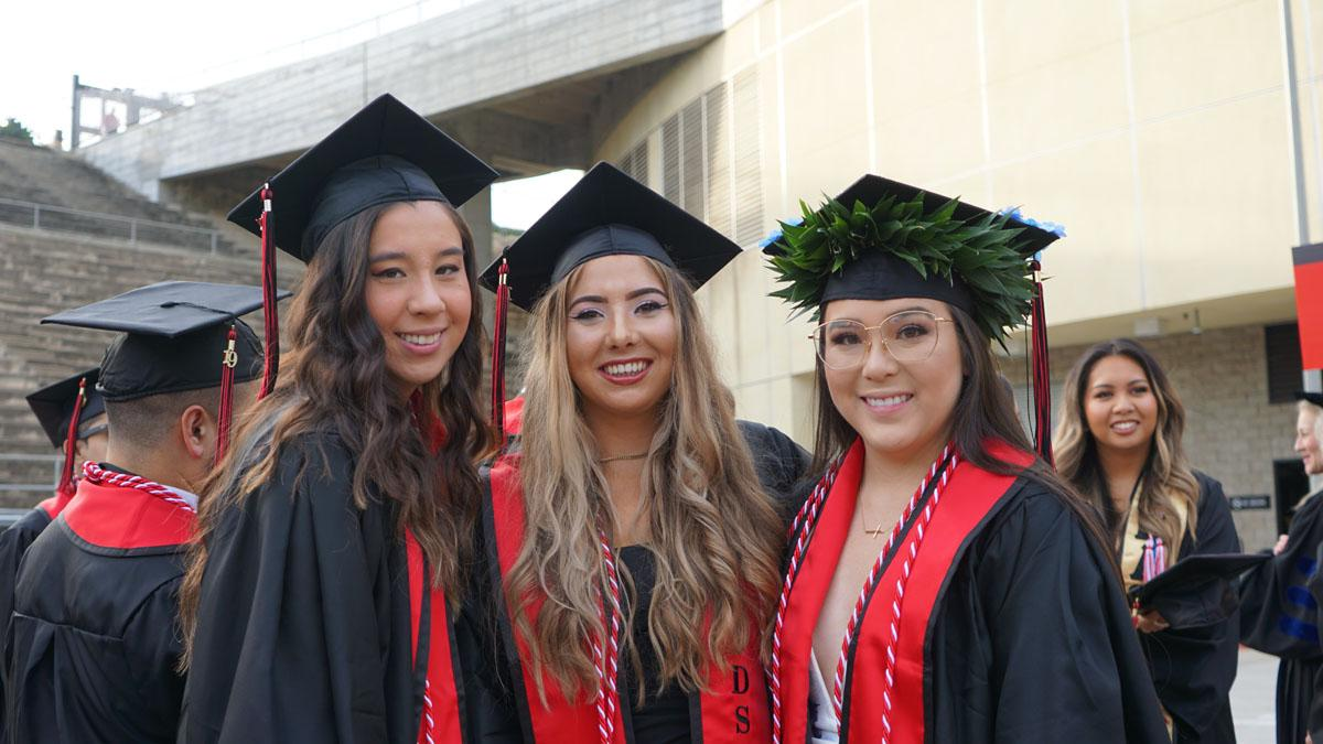 Three students in graduation cap and gowns