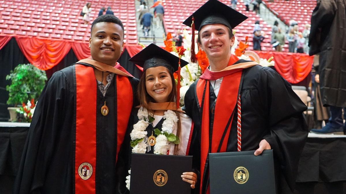 Three students with their diplomas in graduation attire