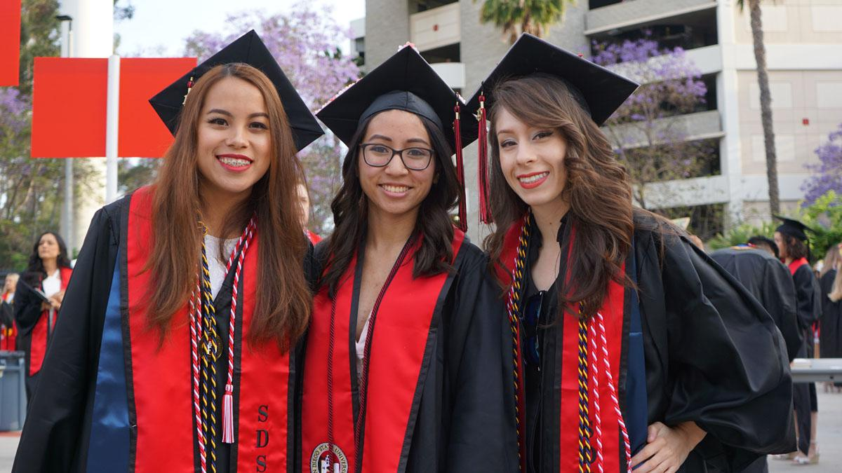 Three students in graduation gowns
