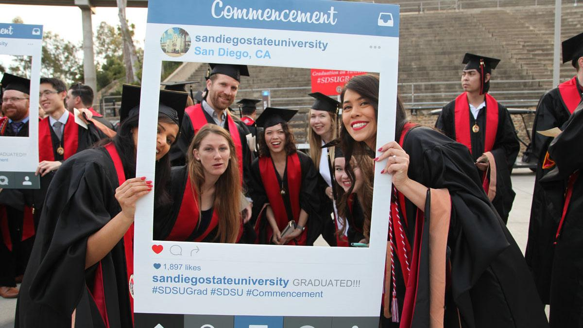 Students posing for photo using prop of social feed post frame