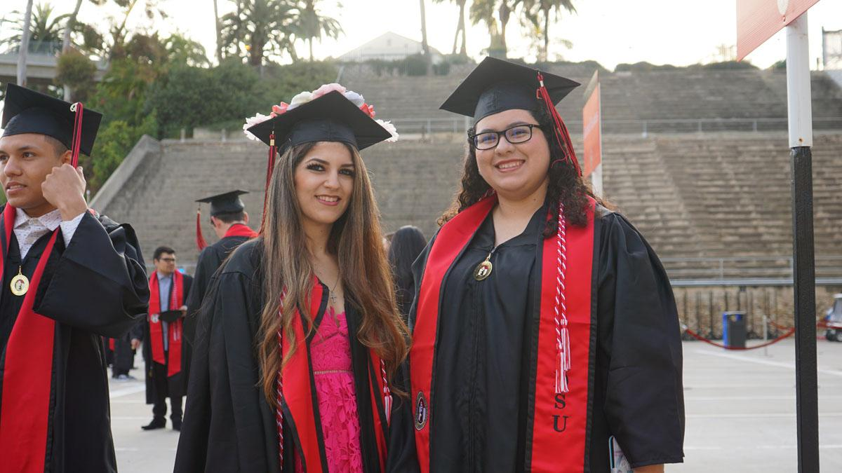 Two students in graduation gowns outside